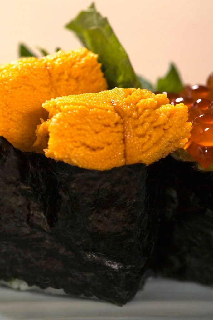 Uni sushi on a plate served with salmon roes.