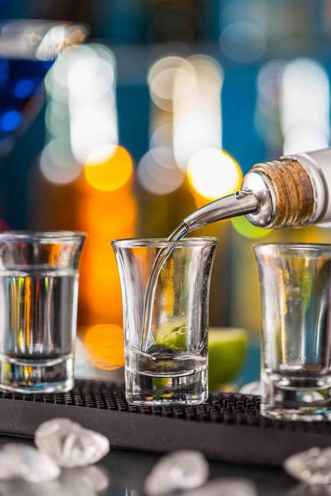 Pouring vodka into a shot glass.