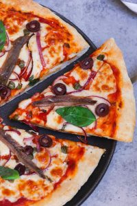 Anchovies on pizza is an Italian classic! My search for the perfect homemade Anchovy Pizza with the best flavor combination is over! This recipe begins with a homemade pizza dough, topped with cured anchovies, olives, capers, onions, and mozzarella cheese. With a few tips, you'll learn how to make a perfect anchovy pizza at home. #AnchovyPizza #AnchoviesOnPizza