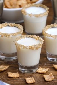Cinnamon Toast Crunch Shot is an adult version of your favorite childhood cereal, in shot form. The base of this delicious alcoholic drink is RumChata and Fireball Whiskey, served in shot glasses rimmed with crushed cinnamon toast cereal. Sweet, boozy, and creamy with a nice cinnamon flavor! #CinnamonToastCrunchShot #CinnamonToastShot #RumChataShot