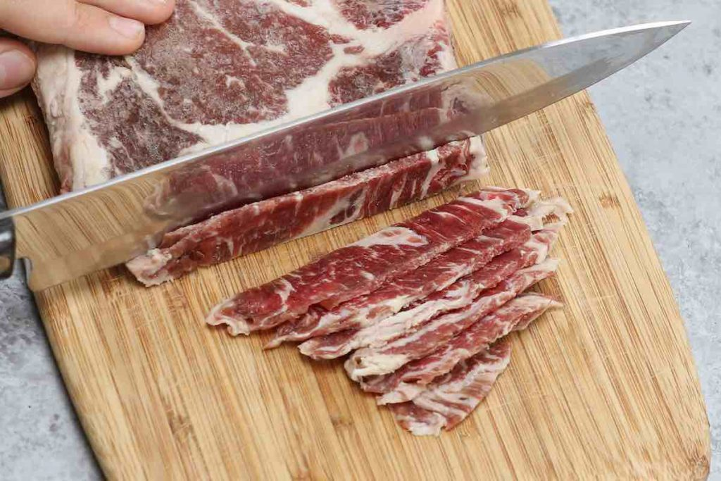 Cutting half-frozen beef into thin slices on a wooden cutting board.