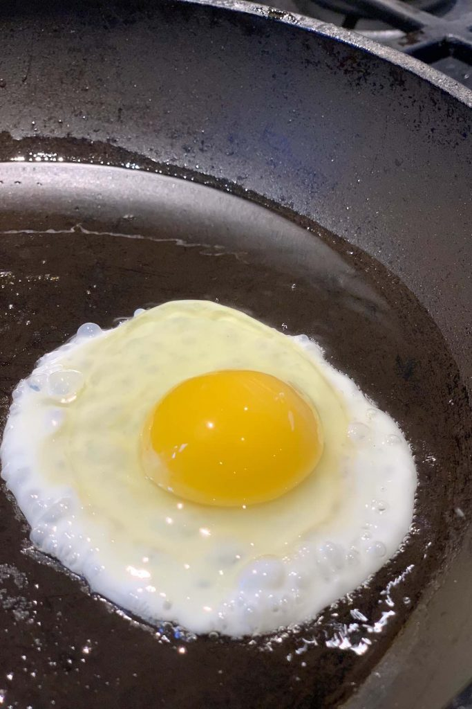 A photo showing the outer layer of the egg white just starts to set while the inner layer around the yolk is still liquid.