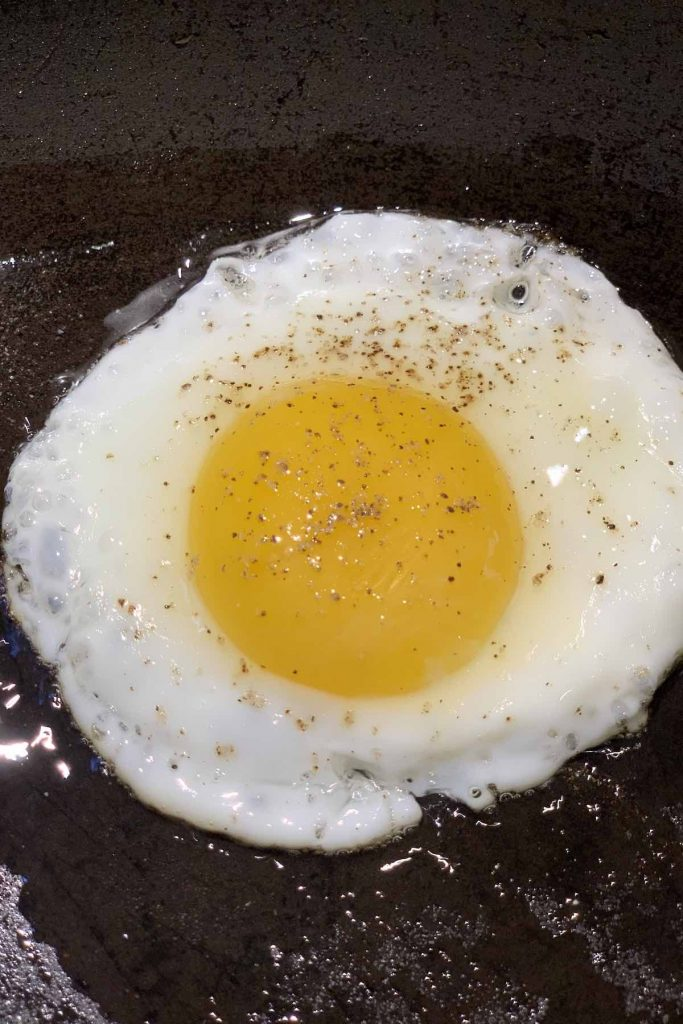 The outer layer of the whites are completely set while a half-inch of the whites surrounding the yolk are starting to set.