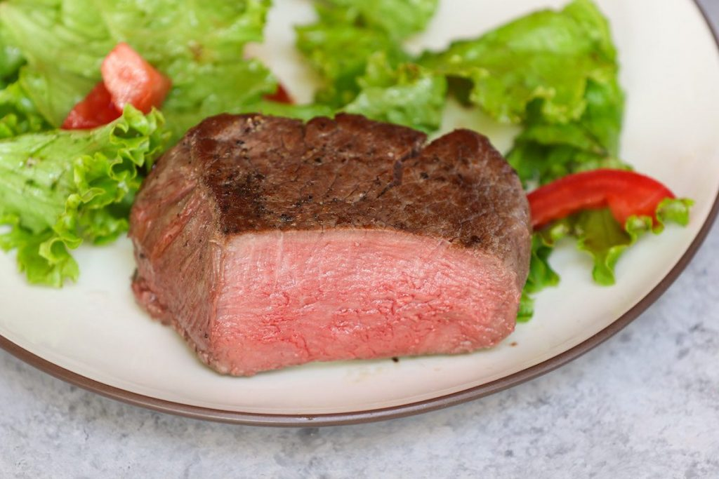 Serving filet mignon with green salad on a white plate.