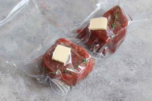 Filet mignon steaks vacuum-sealed in a zip-top bag.