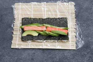 Placing fillings on top of the nori.