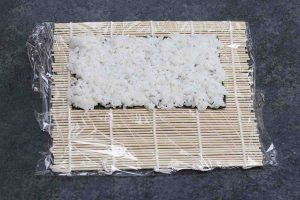 Spreading a thin layer of rice on top of the nori.