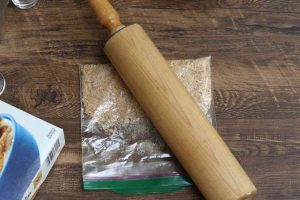 Crushing the cinnamon toast crunch cereal using a rolling pin.