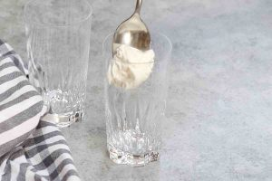 Adding marshmallow-infused whipped cream to the bottom of a glass.
