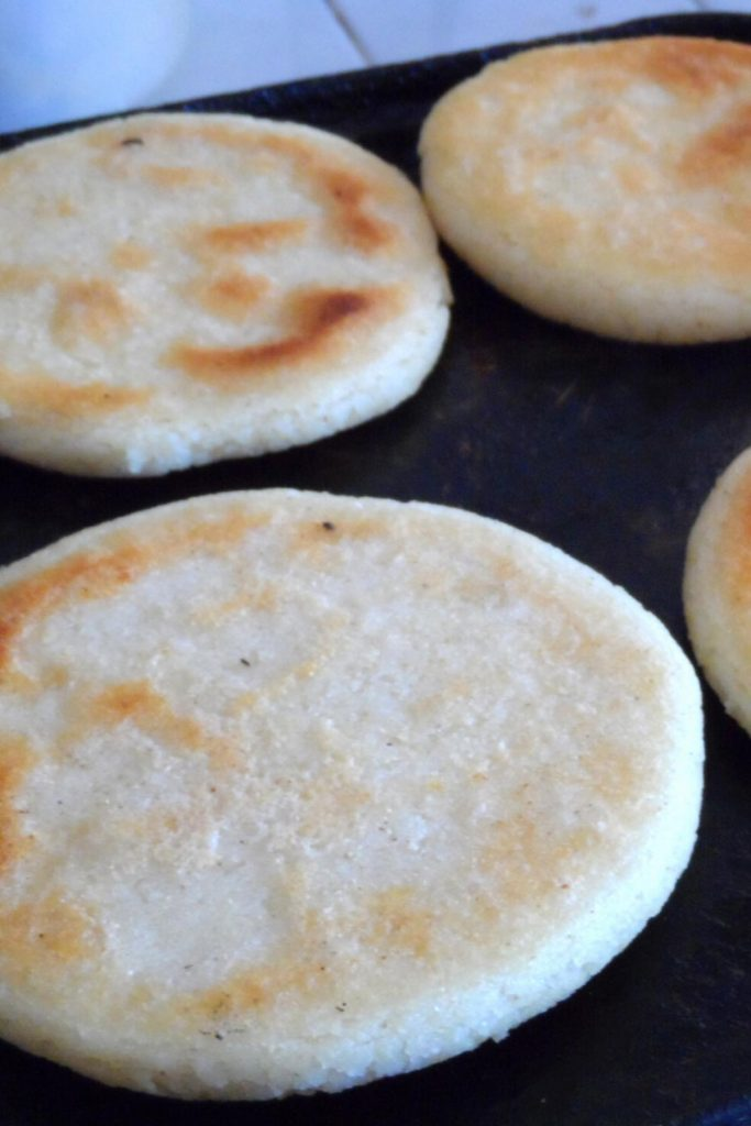 Cooking arepa paisa thin disks.