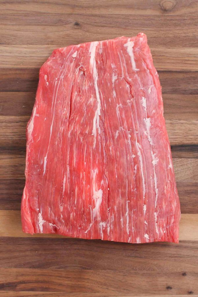 A piece of raw flank steak on the counter.