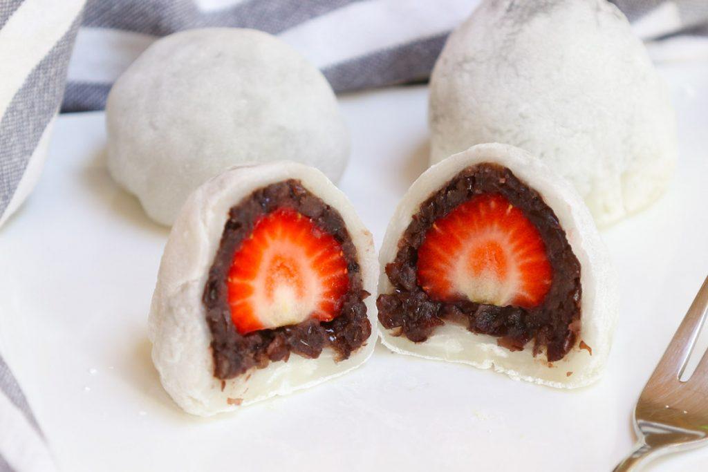 Strawberry daifuku on a white plate.