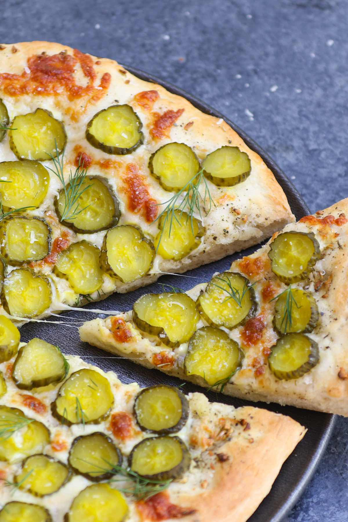 Pickles on Pizza! I never thought I'd like the idea, then once upon a time I tried Dill Pickle Pizza with garlic sauce. It changed my entire outlook on pickle pizza. The combination of cheesy, garlicky, and tangy flavors is seriously good! And there's ranch on the side for dipping. #PicklePizza #DillPicklePizza