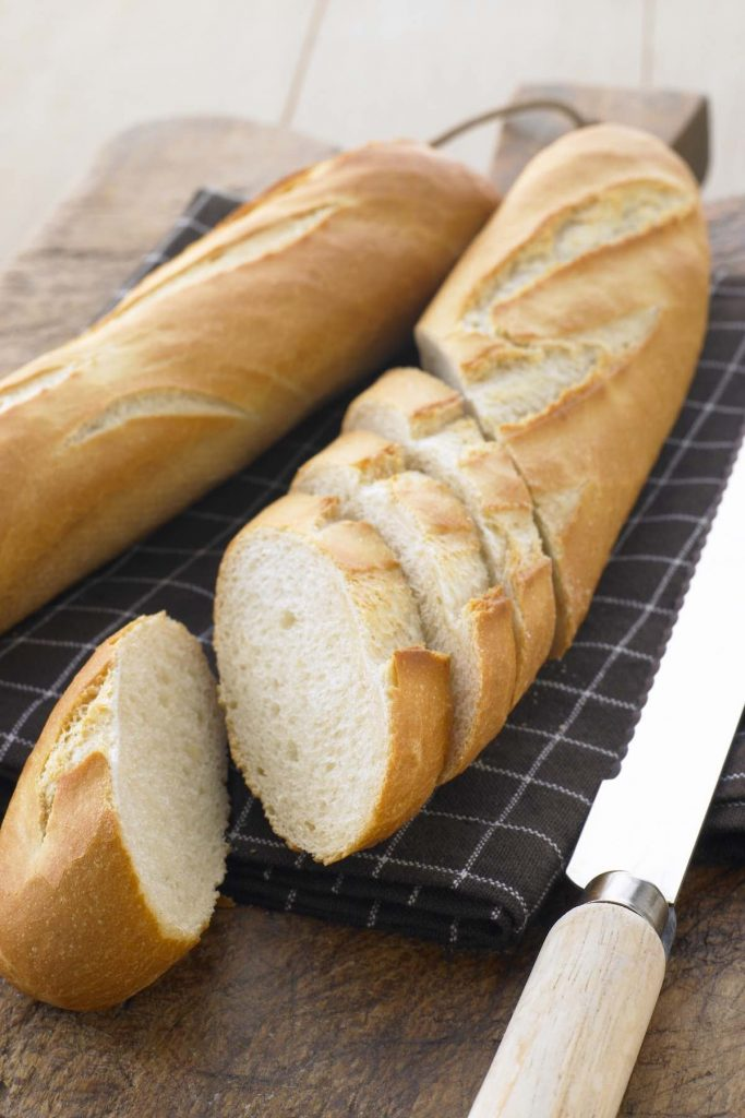 Cutting a baguette into 1/4-inch thick slices.