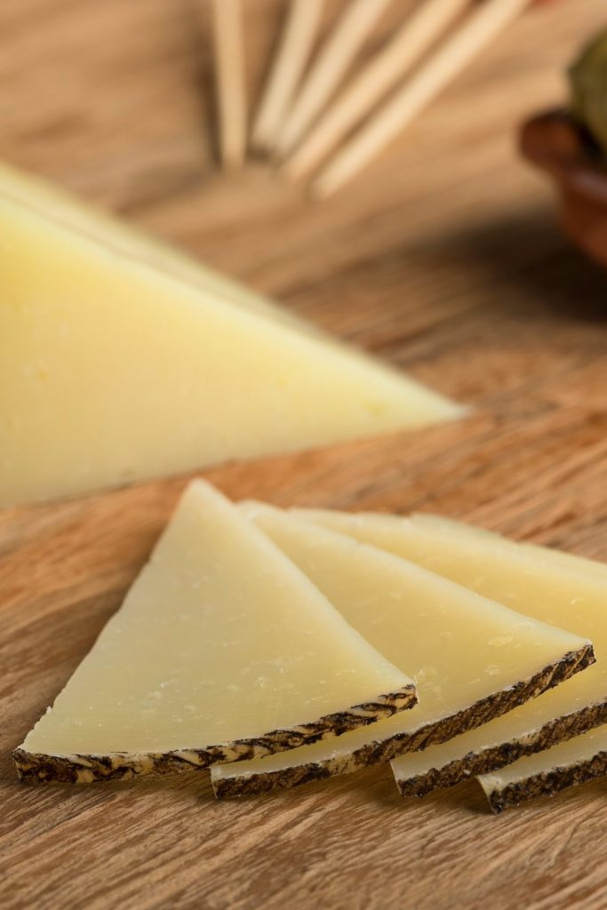 Cutting queso manchego cheese into thin slices.