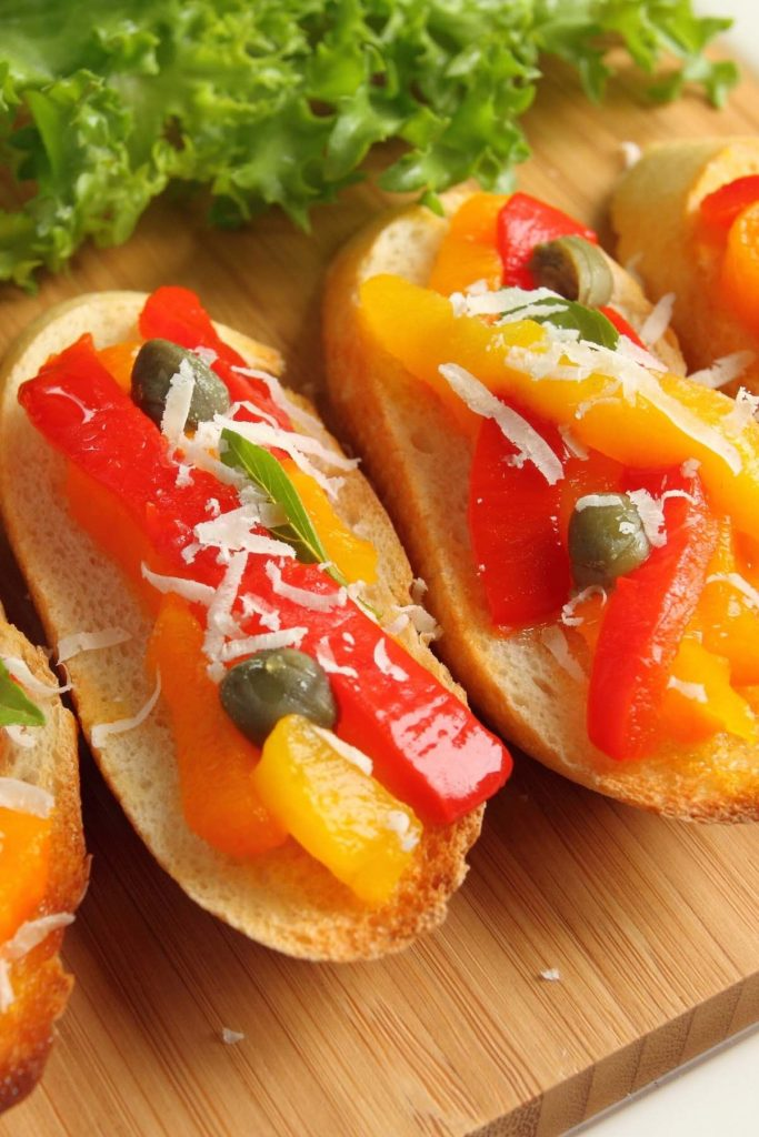 Crostini topped with roasted bell peppers, shredded queso manchego cheese, and capers.