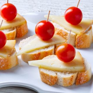 This Queso Manchego Crostini is an easy and delicious appetizer made with simple ingredients that pack in some big flavors! All you need is sliced bread, olive oil, Spanish Queso Manchego, and other favorite toppings to make a party platter or delightful finger food. #QuesoManchego #ManchegoCheese #Crostini