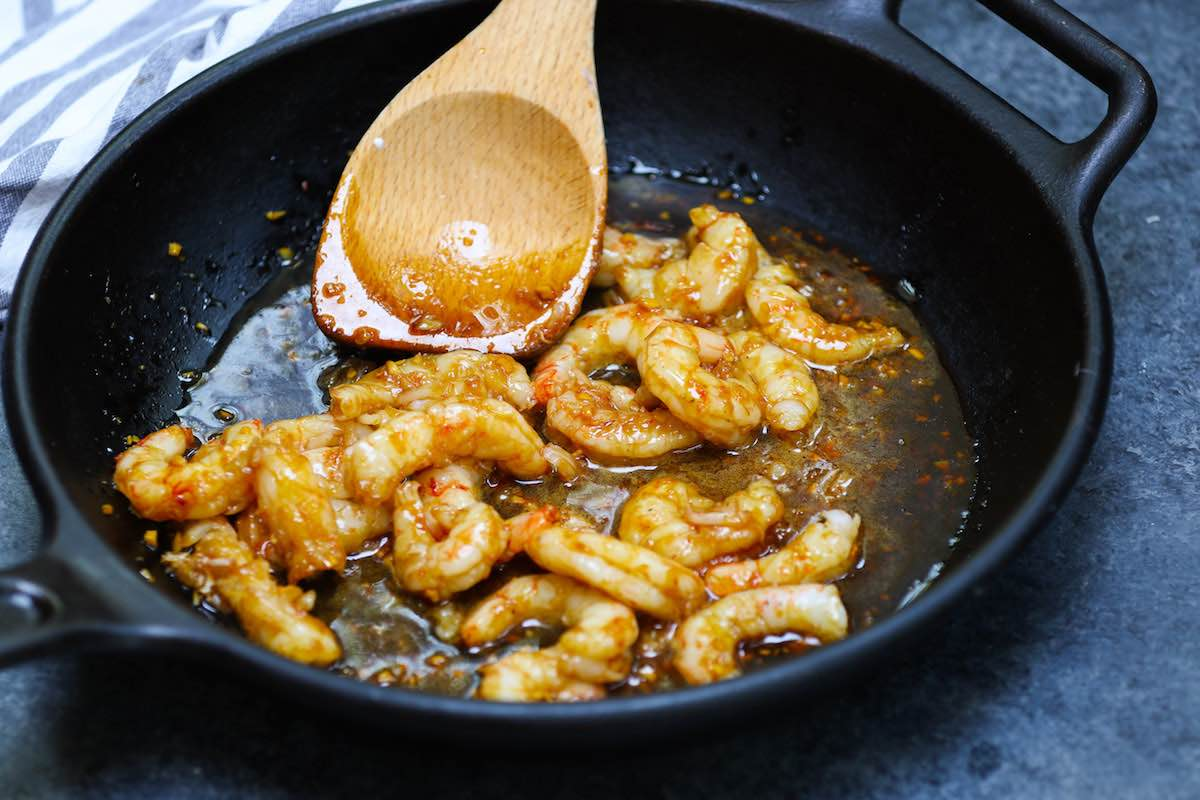 Tossing the cooked shrimp with honey garlic sauce.