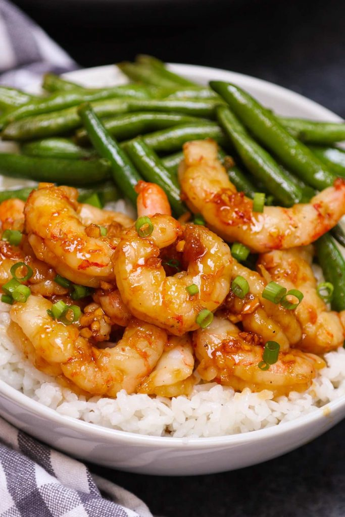 Sous vide honey garlic shrimp served with green beans over rice in a white bowl.