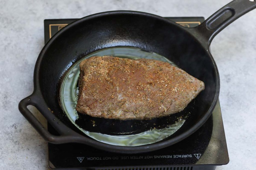 Searing sous vide cooked tri tip in a skillet.