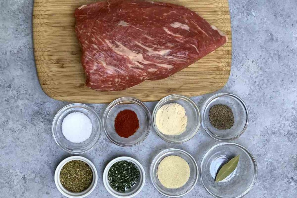 Tri tip and seasoning ingredients on the counter.