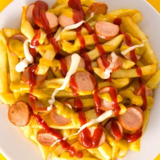 Salchipapas is local Peruvian street food. But you can easily make it at home with homemade French fries and pan-fried beef sausages. This fast food is perfect for parties, game days, or other special occasions when you crave a tasty and comfort appetizer or meal. #Salchipapa #Salchipapas