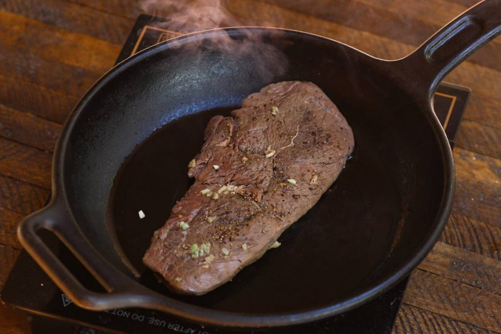 Searing the sous vide cooked steak in a hot skillet.