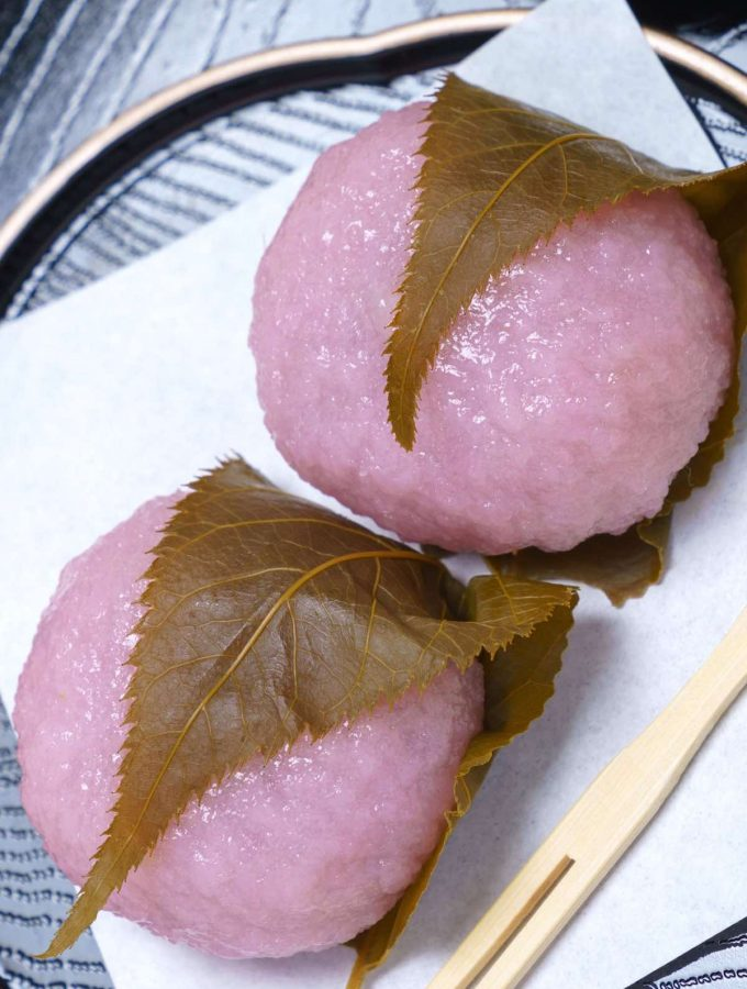 Easy Sakura Mochi with chewy and sticky rice cake on the outside, and sweet red bean paste filling on the inside! It's rolled into beautiful pink mochi balls and covered with an edible pickled cherry blossom leaf. This Japanese dessert recipe is quick to make at home and perfect for celebrating the spring season or other special occasions. #SakuraMochi #PinkMochi