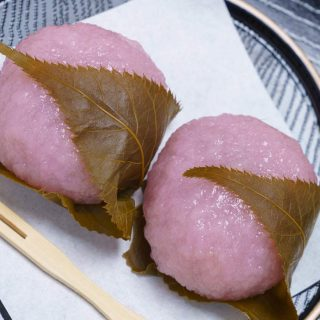 Easy Sakura Mochi with chewy and sticky rice cake on the outside, and sweet red bean paste filling on the inside! It's rolled into beautiful pink mochi balls and covered with an edible pickled cherry blossom leaf. This Japanese dessert recipe is quick to make at home and perfect for celebrating the spring season or other special occasions.