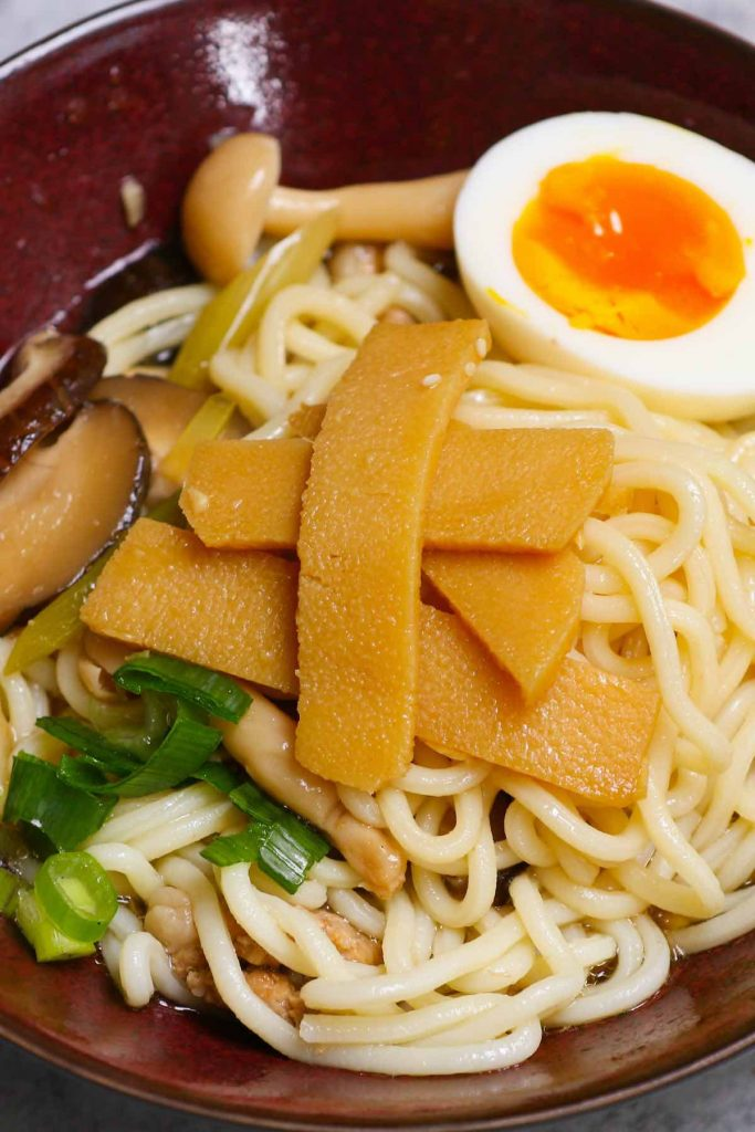 Photo showing menma served as a topping for ramen noodles in a red Japanese bowl.