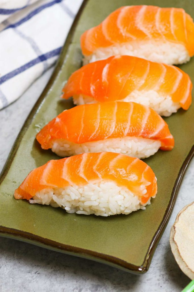 Salmon Nigiri made with sashimi-grade salmon with fluffy sushi rice! It's so much cheaper than the restaurant, and incredibly easy to make at home. I'll share with you the secrets to filet and cut salmon for nigiri sushi or sashimi with step by step photos and a video. #salmonNigiri #nigiriSushi