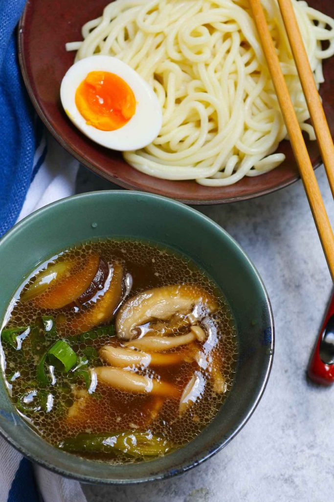Cold ramen noodles topped with soft eggs, and served with tsukemen broth in separate bowls.