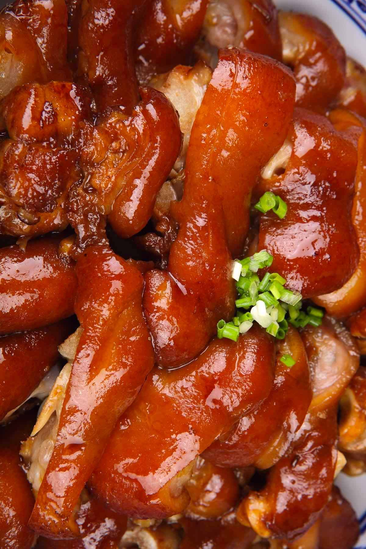 Braised Pig's Feet are tender, juicy, and flavorful – cooked long and slow in a rich sauce. Pig feet or pig trotters are considered one of the most delicious parts of pork. My family makes this recipe for regular weekdays and special occasions like Chinese New Year. Serve them with mashed potatoes and green vegetables for an amazing meal! #PigFeet #PigFeetRecipe #PigTrotters #PorkFeet