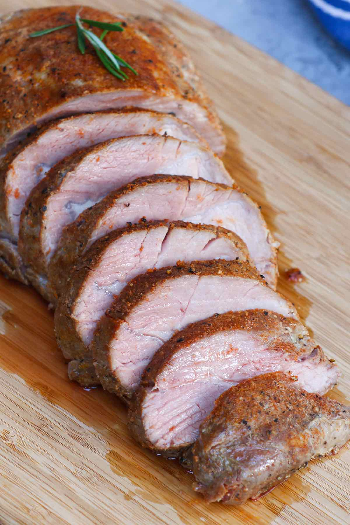 Sliced sous vide pork loin served on a wooden cutting board.