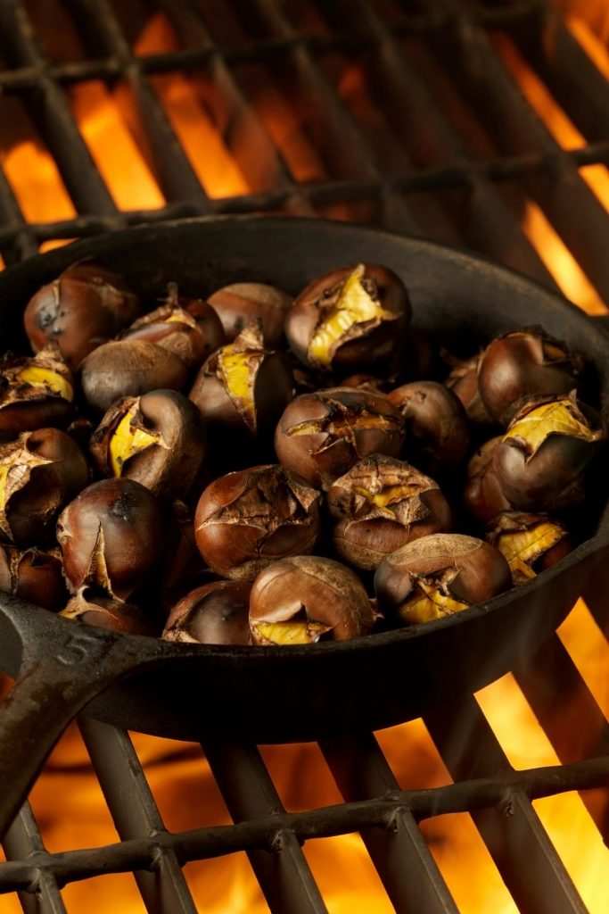 Closeup showing chestnuts roasting on an open fire.