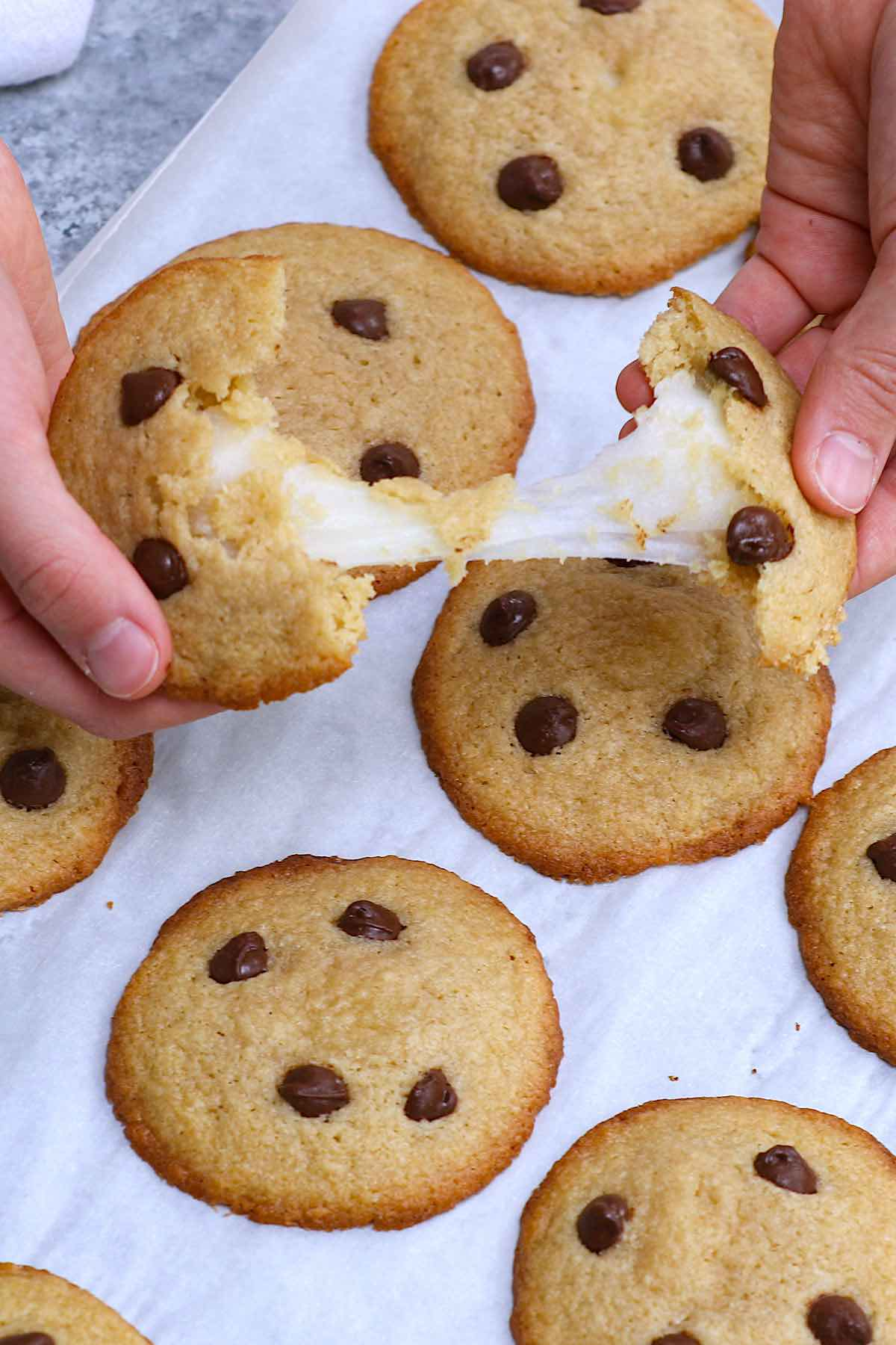 Mochi Cookies, who could resist them? Sweet and sticky mochi dough on the inside; soft and chewy cookies on the outside, packed with chocolate flavor! This mochi stuffed chocolate chip cookies recipe is quite easy to make, and you can customize the cookie dough with different flavors like Matcha green tea or peanut butter. #MochiCookies