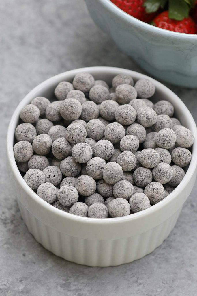 Closeup of uncooked tapioca pearls in a small white bowl.