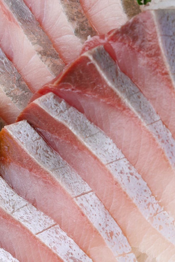 Slicing the raw yellowtail fish into uniform thin slices.