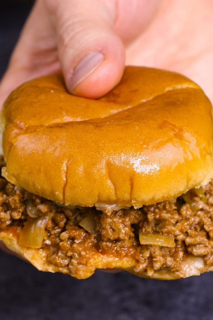 Closeup showing holding sloppy joes.