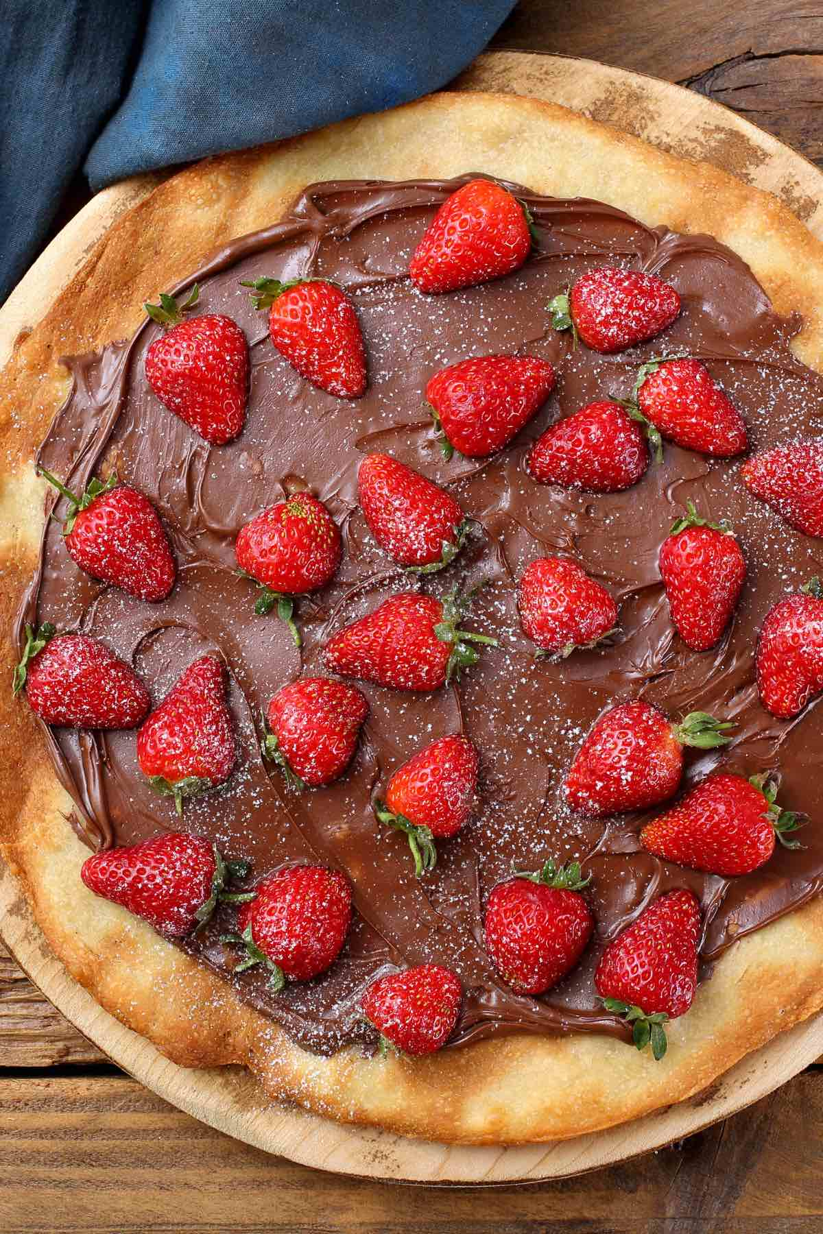 This Nutella Pizza is a must-try dessert that's sure to impress your guest. It's perfectly easy to make – this recipe skips out on the tomato and cheese in favor of adding chocolate spread onto the pizza crust, making a mouth-watering dessert. You can easily customize it with different topping ideas like strawberries, bananas, or marshmallows.