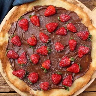This Nutella Pizza is a must-try dessert that's sure to impress your guest. It's perfectly easy to make – this recipe skips out on the tomato and cheese in favor of adding chocolate spread onto the pizza crust, making a mouth-watering dessert.