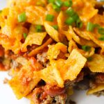 Take everything you love about a taco salad and turn it into a warm, cheesy, baked Walking Taco Casserole! The entire family will love this Tex-Mex recipe, with its succulent ground beef, gooey cheddar cheese and crunchy Fritos, Doritos, or Tortilla Chips. It's easy to assemble ahead of time and bake later for a quick dinner!