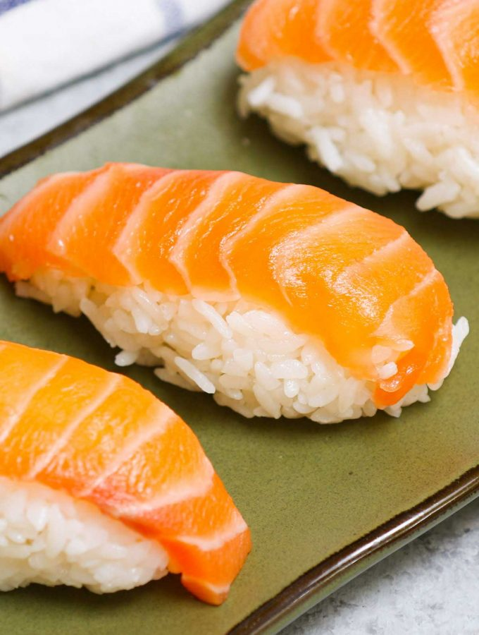 An easy and complete homemade Nigiri tutorial with lots of tips and tricks. Unlike maki sushi, nigiri isn't rolled. Instead, it's comprised of a thin slice of raw or cooked seafood like salmon or shrimp atop a mound of vinegary rice. You'll learn everything about Japanese nigiri including the difference between nigiri and sashimi, and how to make perfect nigiri at home.