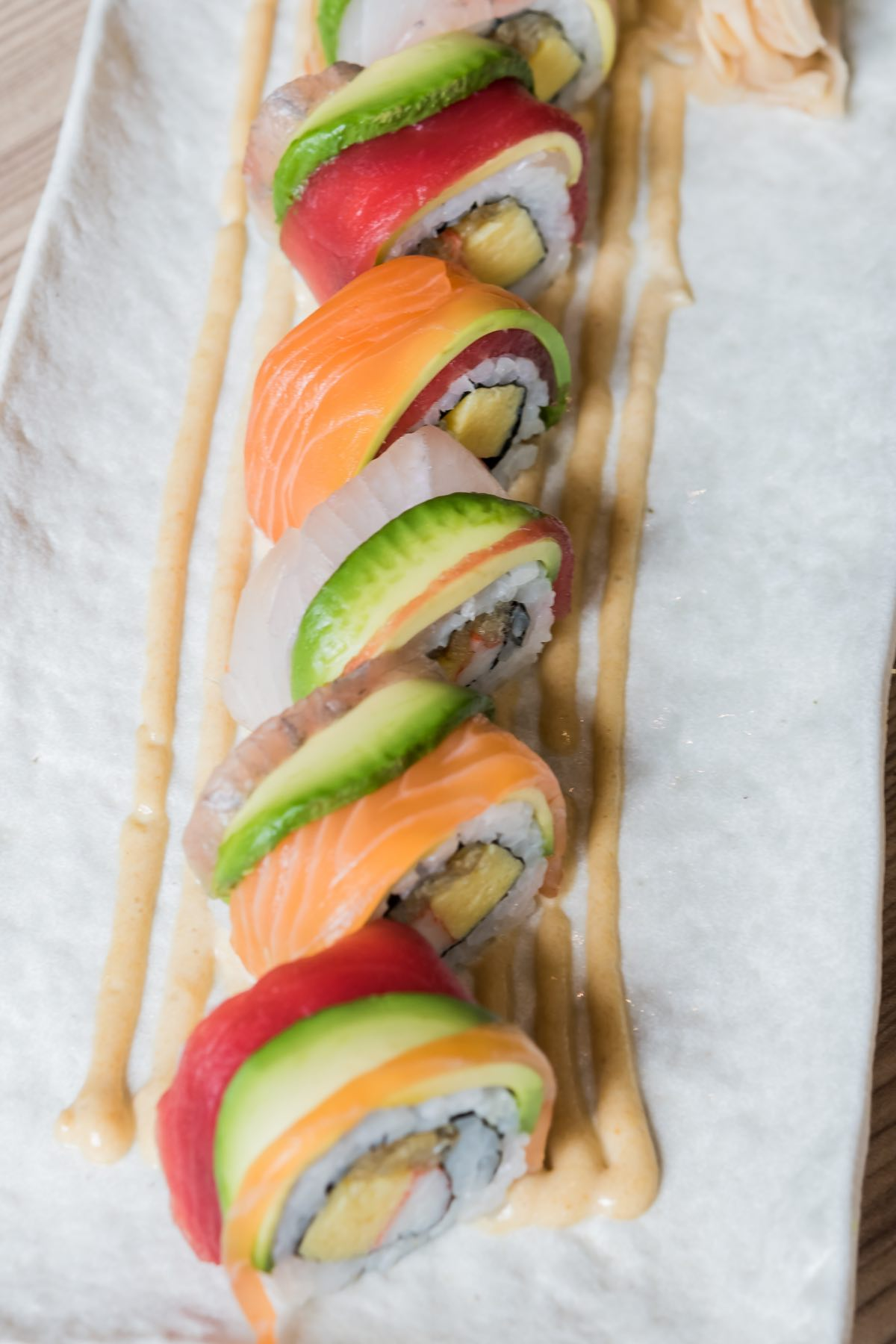 The Rainbow Roll is one of the most popular sushi items at many Japanese restaurants. It's uramaki sushi with the rice on the outside, covering seaweed nori, and filled with creamy avocado and imitation crab. Atop the rainbow sushi roll is a colorful assortment of fresh fish such as salmon, tuna, yellowtail, together with slices of avocado. This roll is a great way to sample many types of fish at once.