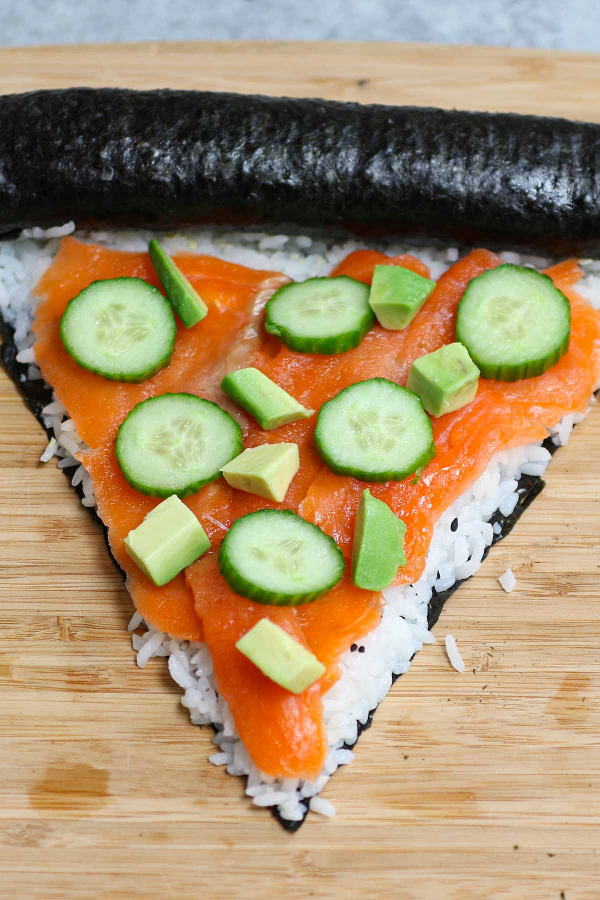 "Here's a way to shake up your pizza night...with Sushi Pizza! Imagine the convenience of a handheld slice of pizza with all of your favorite sushi flavors. This recipe makes a ""crust"" out of seaweed and rice that can be topped with all of your favorite sushi fixings like salmon, avocado, and cucumber."