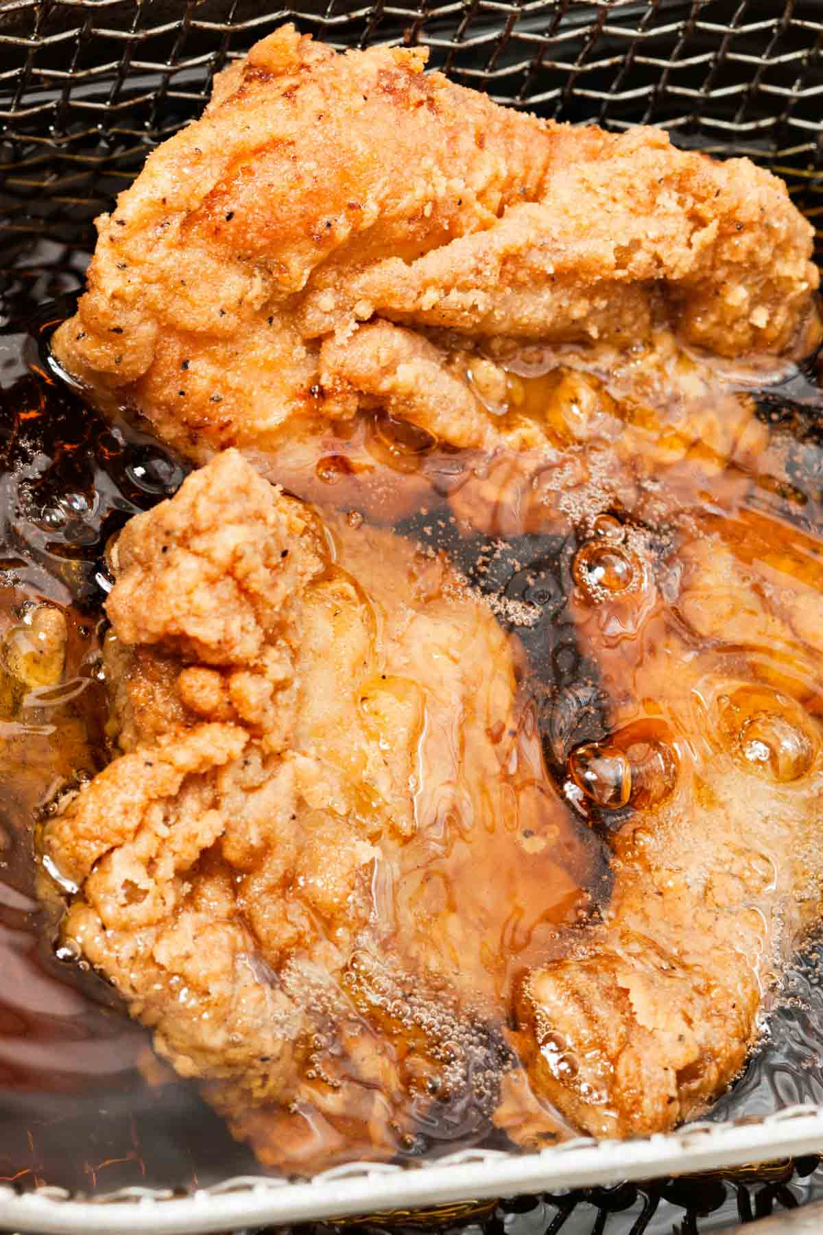 Closeup showing how to deep fry chicken fillet.