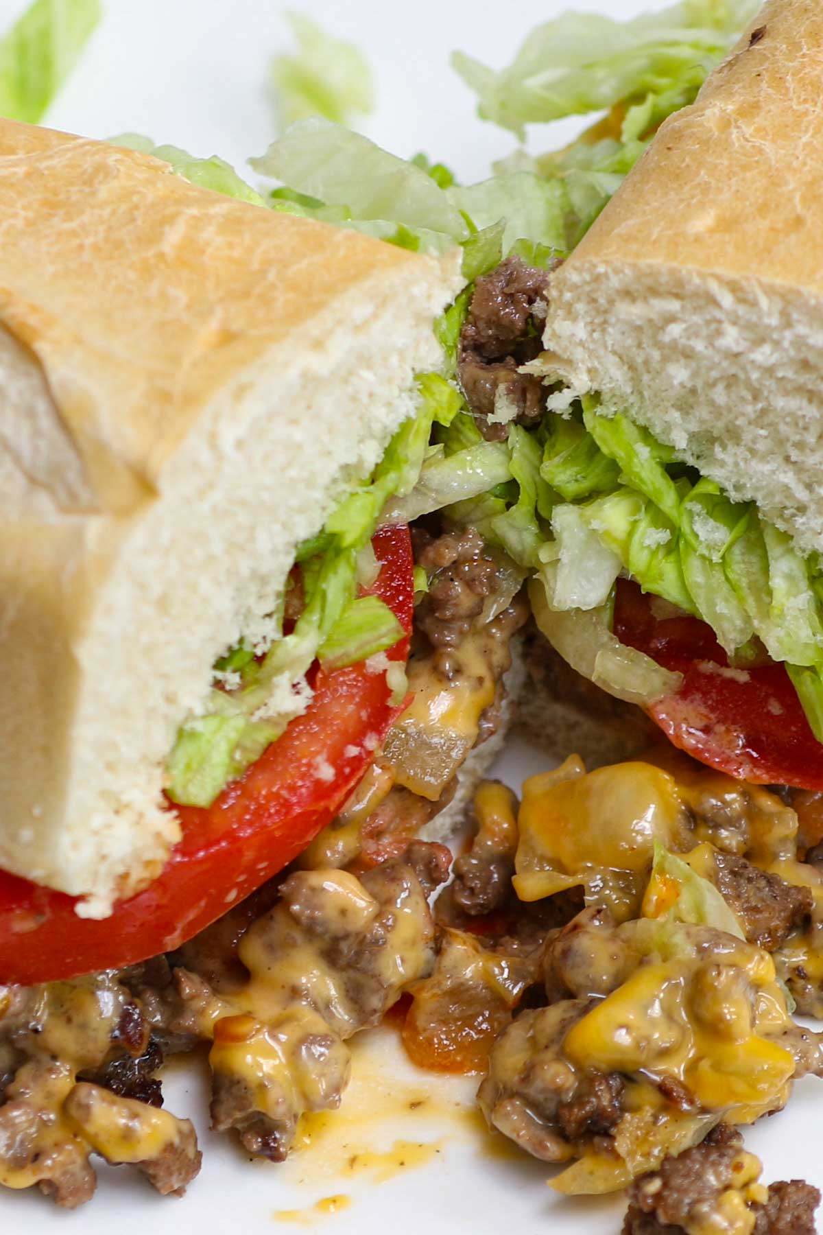 New York City's Chopped Cheese Sandwich with chopped beef burgers, melted gooey cheese, caramelized onions, topped with tomatoes and shredded lettuces, and hugged by a toasted hero roll. This is the classic way to make the iconic NYC chopped cheese. It reminds me of Philly cheesesteak, but even better!