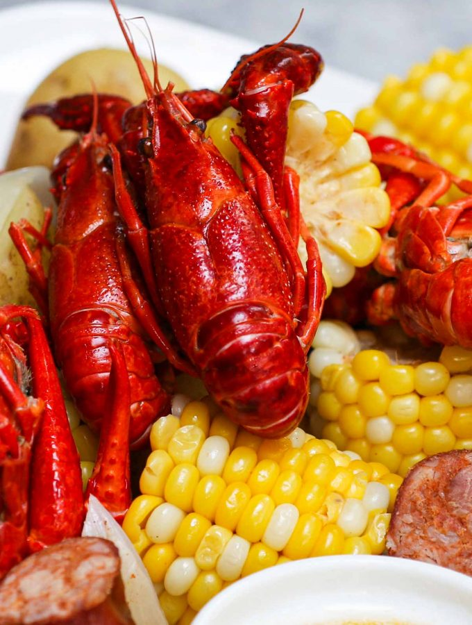 This Louisiana Crawfish Boil contains crawfish, corn, potatoes, and smoked sausage, all boiled in Old Bay seasoning flavored Cajun-style broth. Serve it with the classic seafood garlic butter sauce for the ultimate crawfish boil recipe.