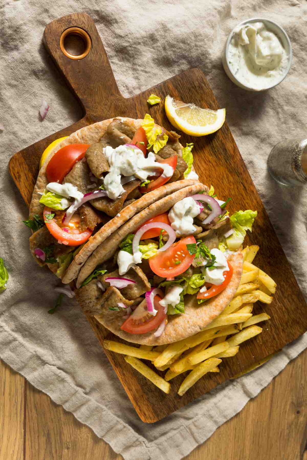 The Easy Greek Gyro Sandwich is gyro meat, fresh vegetables, and feta cheese wrapped in warm pita bread. You can top it with Tzatziki sauce, and it's the ultimate sandwich for Greek food lovers!