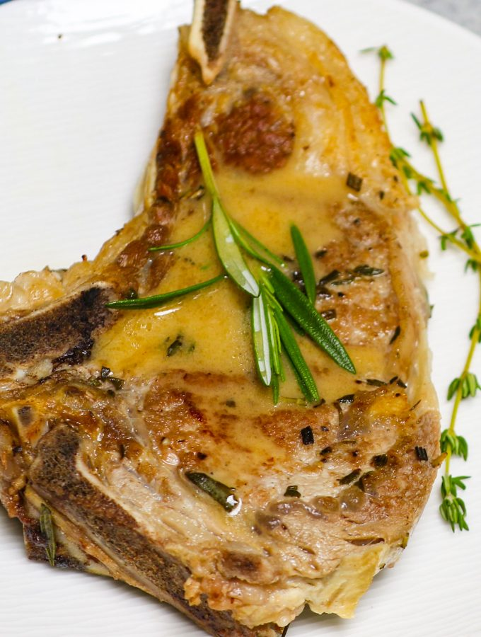 These Veal Chops are quick and easy to make, with a taste that's worthy of a Michelin star. Bone-in veal chops are marinated with fresh rosemary, thyme, salt, and pepper, then tenderized to succulent perfection! Drizzle them with homemade rosemary butter sauce for the most delicious dinner!